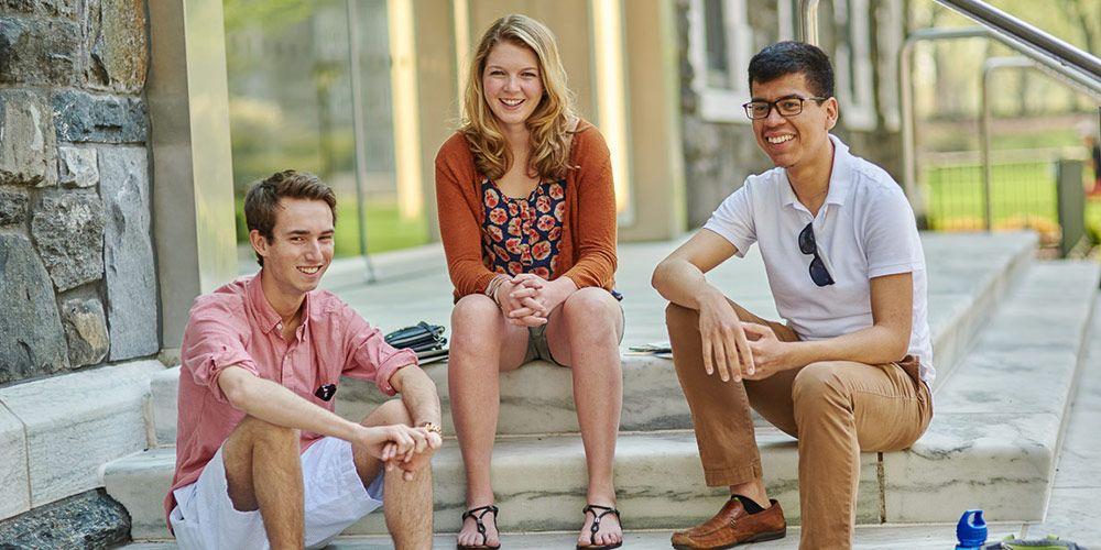 Undergraduate students sitting on sidewalk